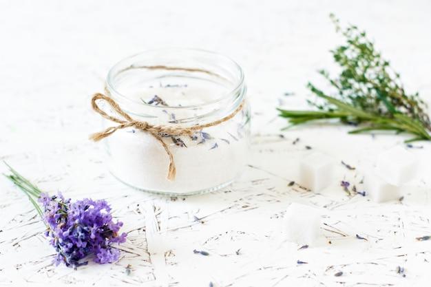 Frasco de vidro com açúcar de lavanda, lavanda fresca sobre um fundo claro de madeira