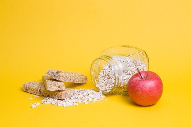Frasco de vidro com aveia, uma maçã e várias barras de proteína para um lanche em uma superfície amarela