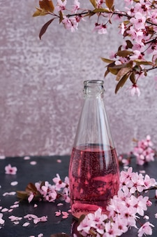 Frasco de vidro com bebida rosa, com ramos de cerejeira em flor acima