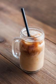 Frasco de vidro com café, ou latte bebida com cubos de gelo e palha.
