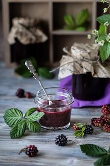 Frasco de vidro com close-up de molho blackberry. ramo com bagas e folhas em uma caixa de madeira esculpida em um escuro de madeira