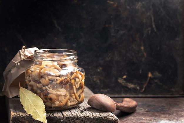 Frasco de vidro com cogumelos em conserva mel agarics e colher de pau na prancha de madeira velha