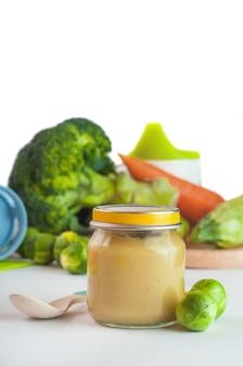 Frasco de vidro com comida natural para bebé isolada vertical