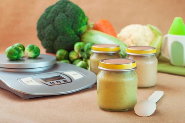 Frasco de vidro com comida para bebê perto da balança de cozinha