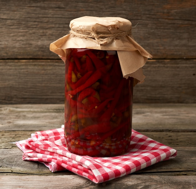 Frasco de vidro com conserva enrolada pimenta vermelha em um fundo de madeira