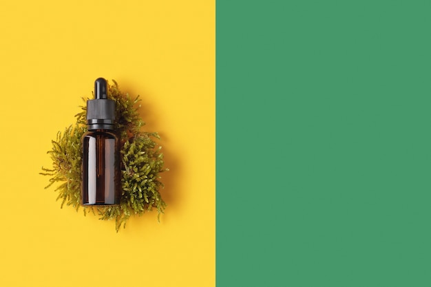 Frasco de vidro com conta-gotas de óleo essencial em musgo amarelo com fundo verde vazio, vista superior. essência líquida para cuidados com a pele ou medicina alternativa.