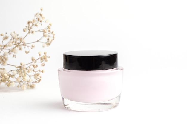 Frasco de vidro com creme facial em um fundo branco e com flores e espaço de cópia