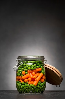 Frasco de vidro com ervilhas e cenouras infantis