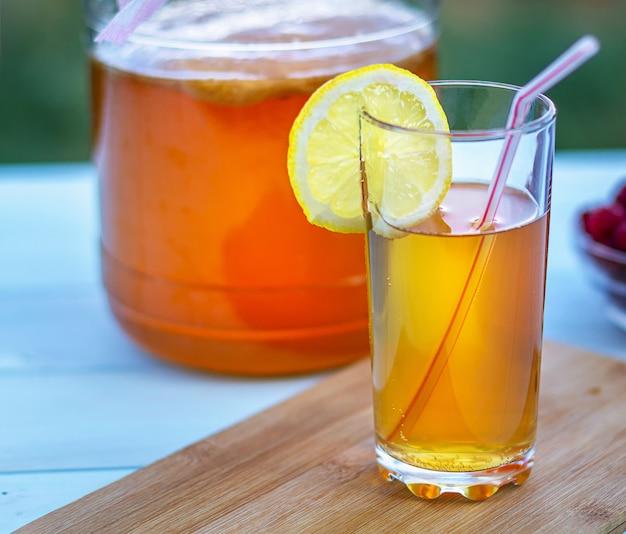 Frasco de vidro com kombucha, copo derramado com kombucha e framboesas no jardim de verão.