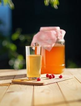 Frasco de vidro com kombuchá copo derramado com kombuchá e framboesas no jardim de verão