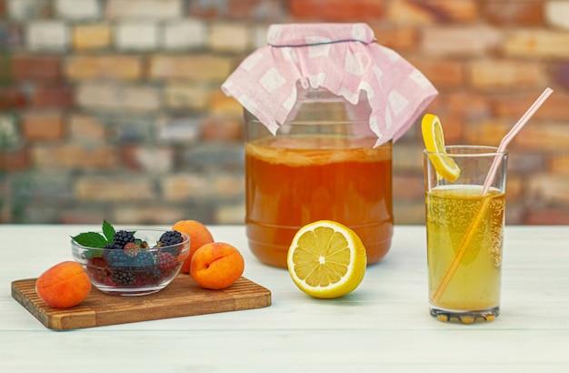 Frasco de vidro com kombucha, um copo derramado com kombucha com uma fatia de limão, frutas em uma placa de madeira
