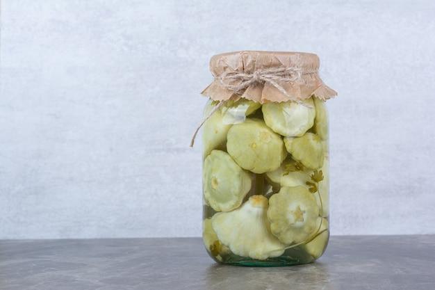 Frasco de vidro com legumes em conserva colocado em mármore