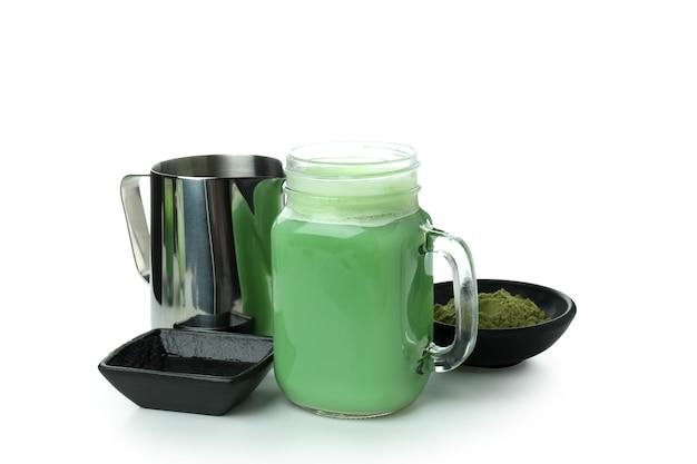 Frasco de vidro com leite matcha e acessórios para fazer, isolado no fundo branco
