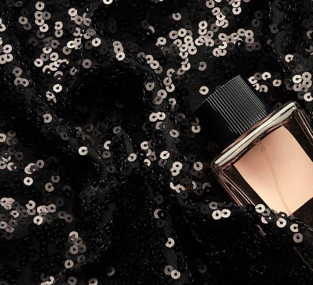 Frasco de vidro com líquido de perfume rosa em fundo preto com lantejoulas brilhantes