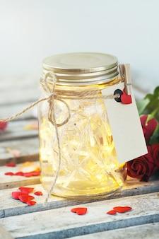 Frasco de vidro com luzes e uma carta amarrado com uma corda