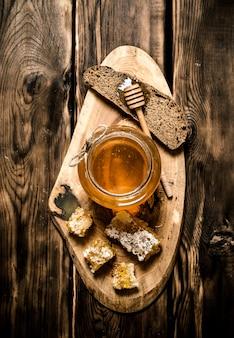Frasco de vidro com mel e um pedaço de pão. em fundo de madeira.