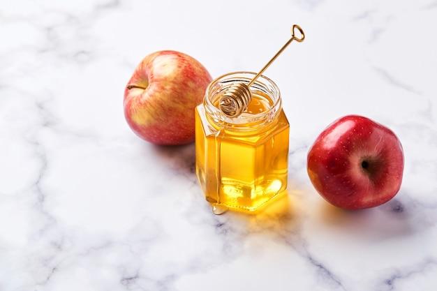 Frasco de vidro com mel líquido floral com colher de mel de metal e duas maçãs vermelhas sobre fundo de mármore claro. substituto alternativo do açúcar, remédio para resfriado e fortalecimento do corpo, superalimento