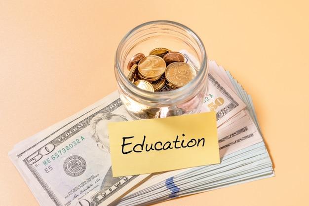 Frasco de vidro com moedas e notas de 50 dólares com etiqueta de educação. conceito financeiro.