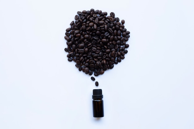 Frasco de vidro com óleo essencial de café e grãos de café em branco