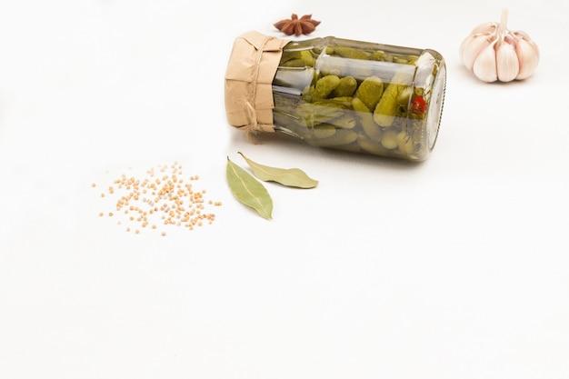 Frasco de vidro com pepinos em lata, sementes de mostarda de alho. copie o espaço