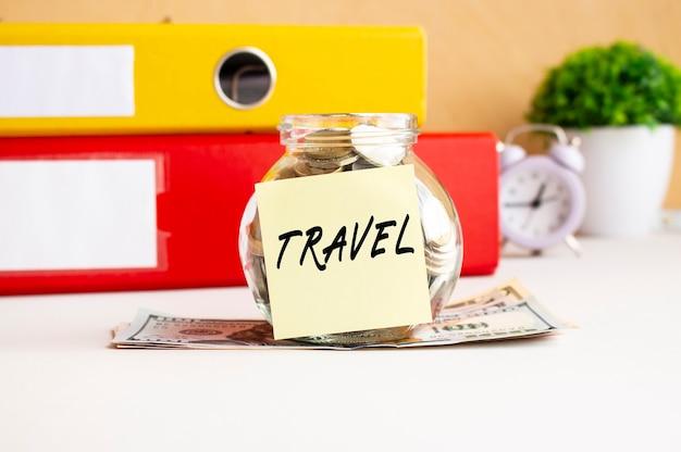Frasco de vidro de cofrinho com moedas fica em uma pilha de notas de dólar na mesa de trabalho. o frasco possui um adesivo com o texto viagem.