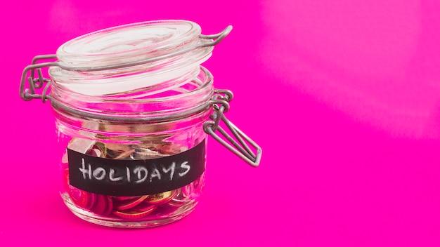 Frasco de vidro de férias com moedas e notas de euro em fundo rosa