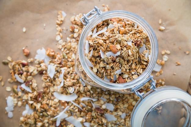 Frasco de vidro de granola orgânica caseira com coco e nozes no fundo de papel manteiga