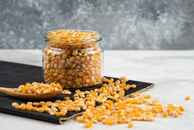 Frasco de vidro de grãos de milho com colher na placa de corte preta.