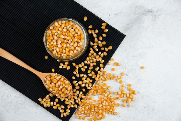 Frasco de vidro de grãos de milho crus com colher na placa de corte preta.