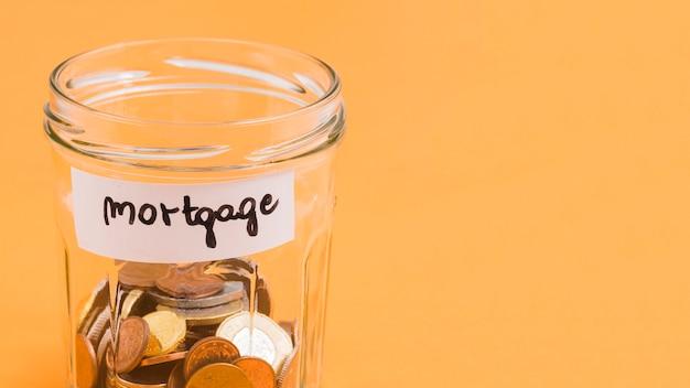 Frasco de vidro de hipoteca com moedas no fundo amarelo