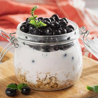 Frasco de vidro de iogurte saudável com mirtilo fresco, aveia e hortelã na mesa de madeira. conceito de café da manhã saudável