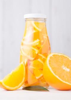 Frasco de vidro de laranja ainda água de frutas e laranjas cruas em branco de madeira
