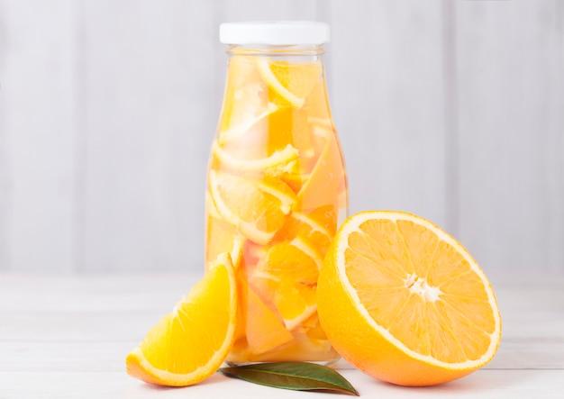 Frasco de vidro de laranja ainda água de frutas na madeira