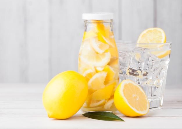 Frasco de vidro de limão ainda frutas limonada de água e copo com cubos de gelo e laranjas cruas em branco de madeira