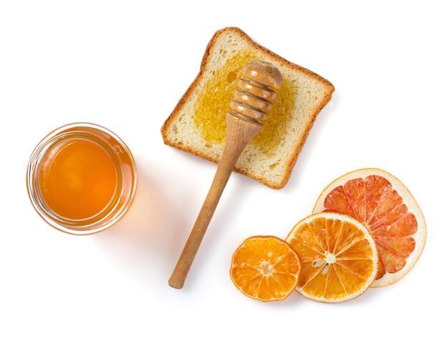 Frasco de vidro de mel e pão isolado no branco