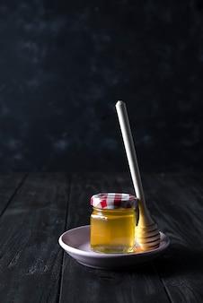 Frasco de vidro de mel e vara em uma placa de cerâmica sobre um fundo escuro de concreto, cópia espaço