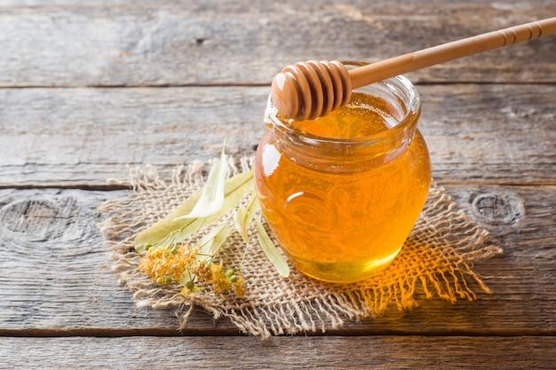 Frasco de vidro de mel, linden flores na superfície de madeira