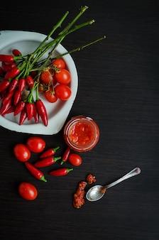 Frasco de vidro de molho de tomate com ingredientes frescos