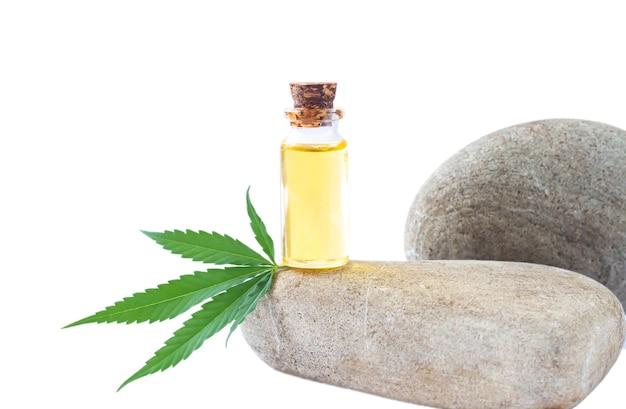 Frasco de vidro de óleo de cânhamo e folha de cannabis isolado no fundo branco