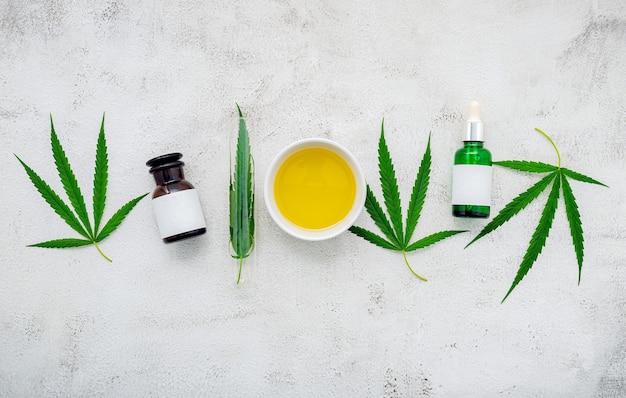 Frasco de vidro de óleo de cannabis e folhas de cânhamo colocadas no concreto.