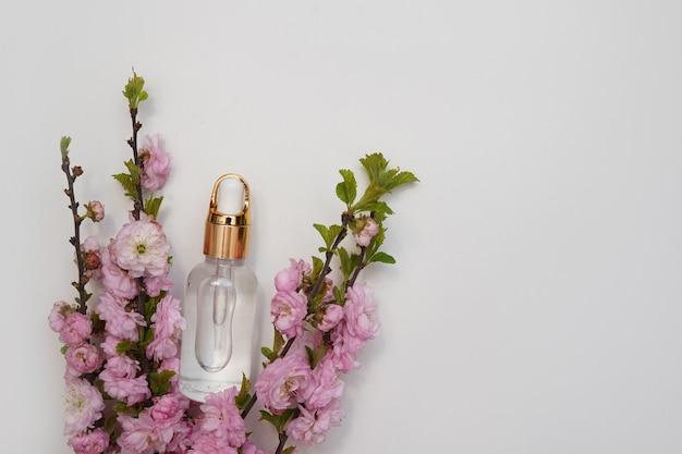 Frasco de vidro de óleo essencial com flores rosa frescas em fundo branco