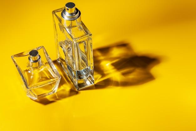 Frasco de vidro de perfume em fundo amarelo claro. eau de toilette
