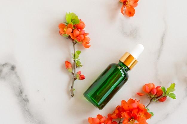 Frasco de vidro de soro com pipeta e lindas flores sobre fundo de mármore. conceito de cosmético spa orgânico natural. vista do topo.