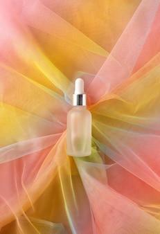 Frasco de vidro de soro com pipeta para produto de beleza em tecido de organza colorido arco-íris. maquete de essência líquida transparente. conceito de higiene de cuidados de saúde