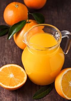 Frasco de vidro de suco de laranja orgânico fresco com laranjas cruas no fundo escuro de madeira