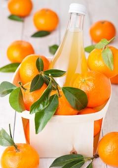 Frasco de vidro de suco de tangerina fresco mandarim em caixa de madeira com fundo de madeira clara