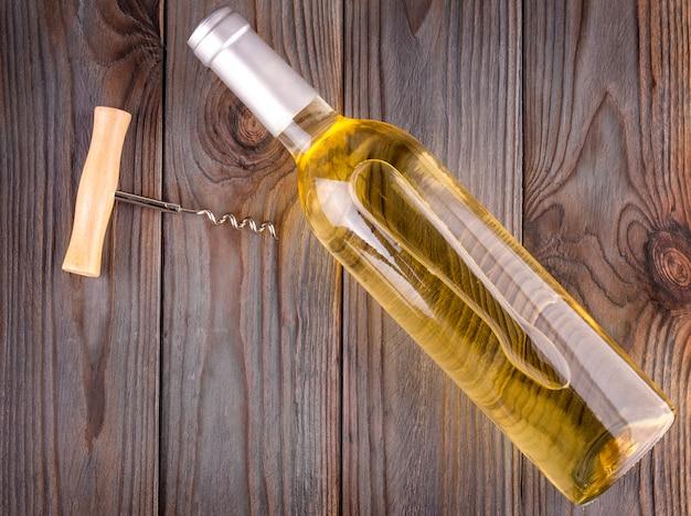 Frasco de vidro de vinho com rolhas no fundo da mesa de madeira.