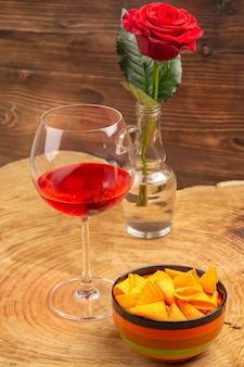 Frasco de vidro de vinho do balão com vista inferior em uma tigela rosa vermelha na superfície marrom