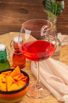 Frasco de vidro de vinho do balão de vista inferior em garrafas vermelhas e verdes de tigela na superfície marrom
