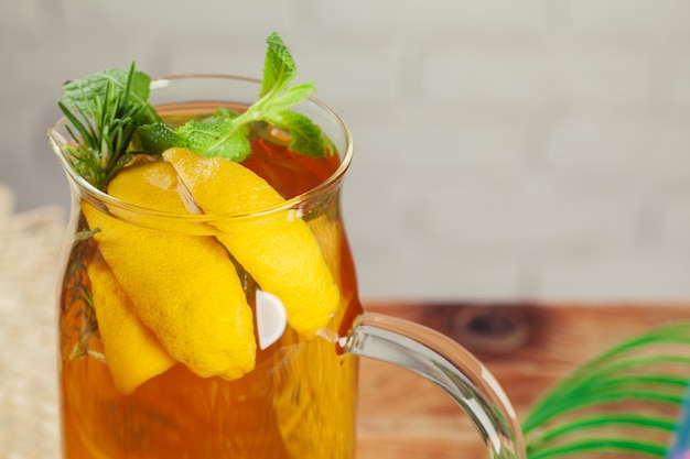 Frasco de vidro do chá verde de gelo com limão, limão, hortelã na mesa de madeira.
